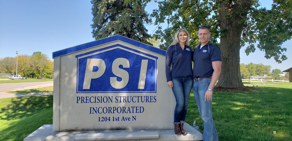 Chris and Nicole Harmsen posing next to the Precision Structures sign.